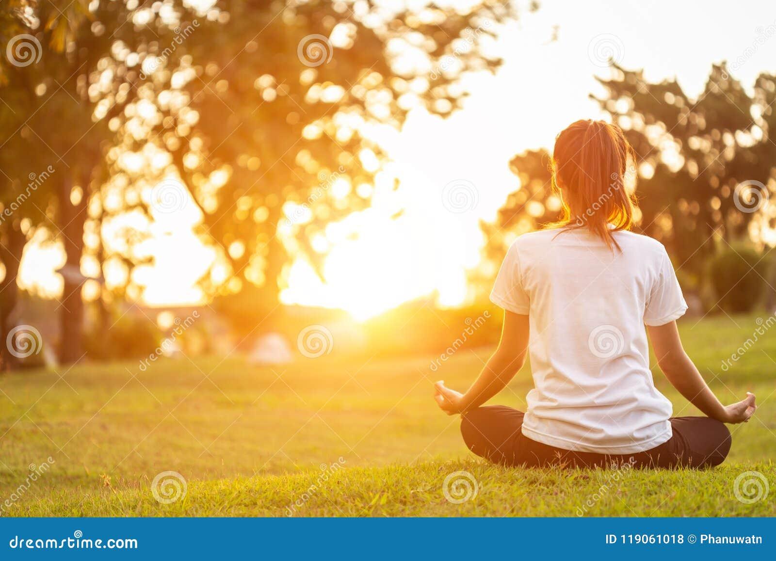 Αρκετά ασιατική γυναίκα που κάνει τις ασκήσεις γιόγκας στο πάρκο