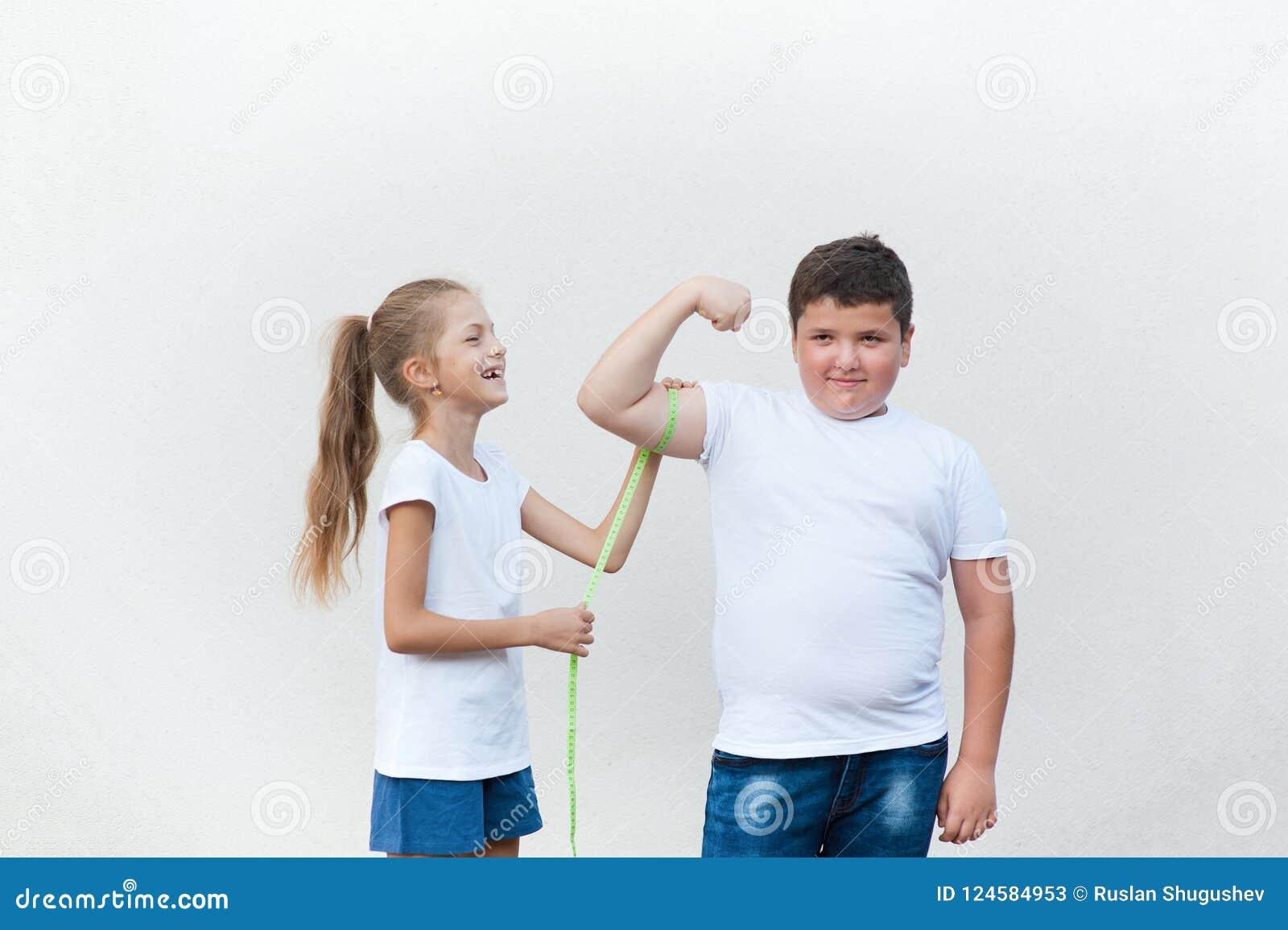 Αρκετά γελώντας λεπτό μικρό κορίτσι που μετρά το χαριτωμένο παχύ μυ δικέφαλων μυών αγοριών με την ταινία
