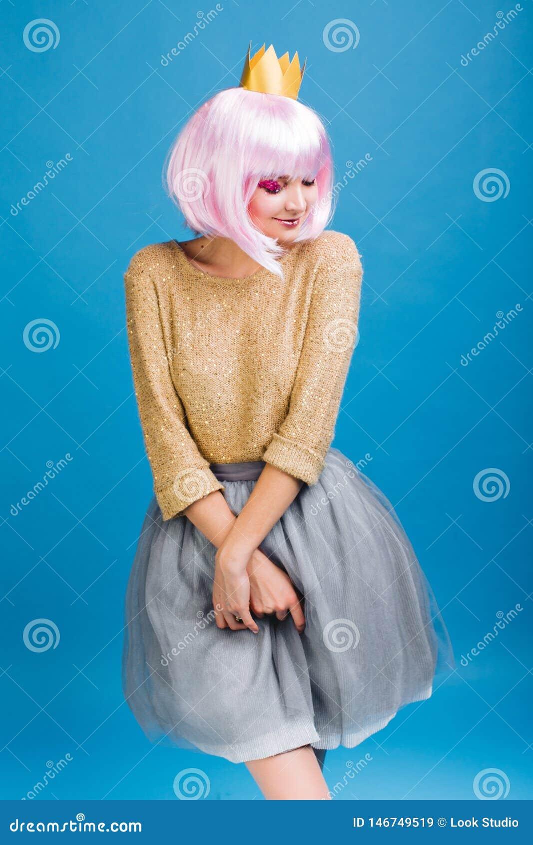 Αρκετά γοητευτική νέα γυναίκα στην γκρίζα φούστα του Tulle, με το ρόδινο κούρεμα στο μπλε υπόβαθρο Χρυσό πουλόβερ, κορώνα στο κεφ