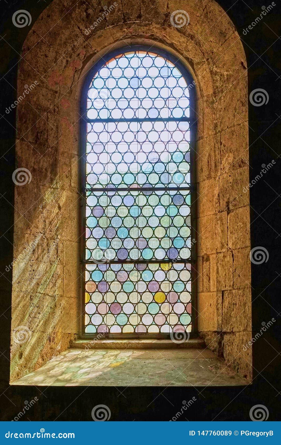 Αρκετά μολυβδούχο λεκιασμένο παράθυρο γυαλιού που τίθεται στους παχιούς τοίχους πετρών