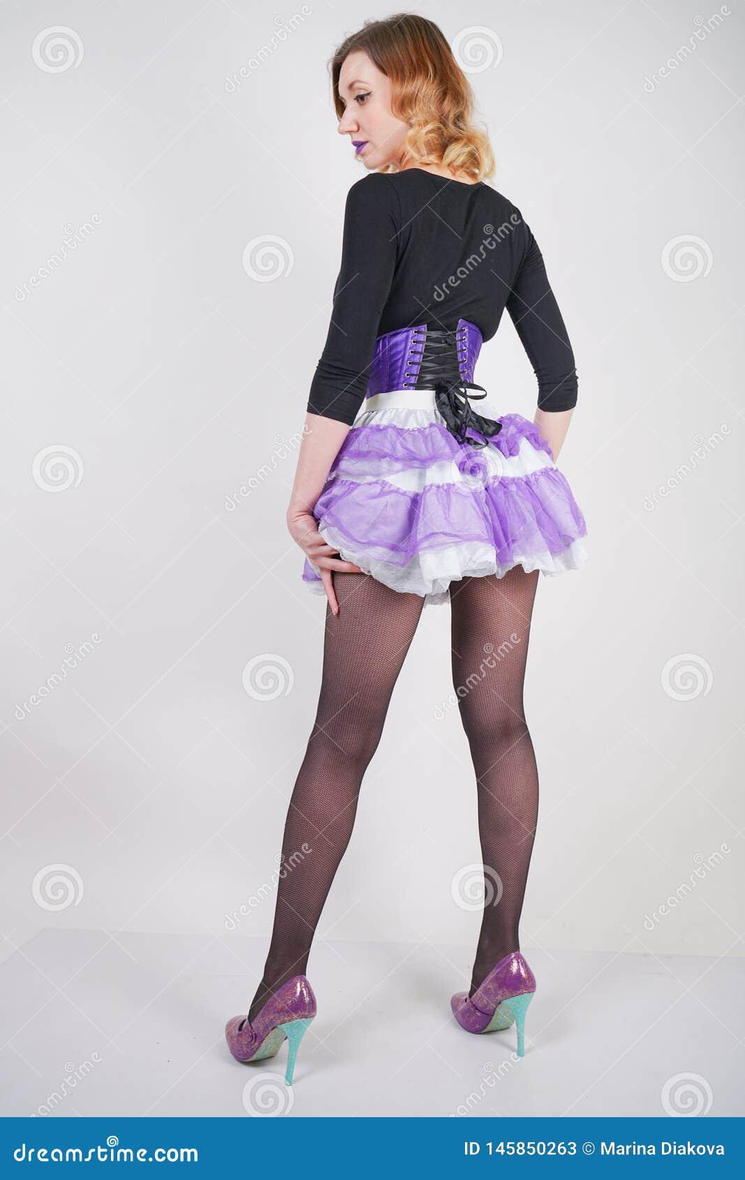Αρκετά μοντέρνο ξανθό κορίτσι που φορά το μαύρο jumpsuit με το πλέγμα pantyhose και τον πορφυρό κορσέ στο άσπρο υπόβαθρο