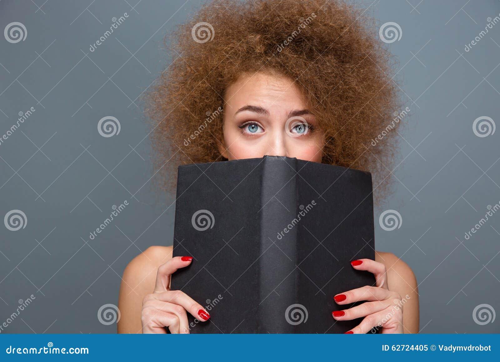 Αρκετά νέα σγουρή γυναίκα που κρύβει ένα βιβλίο