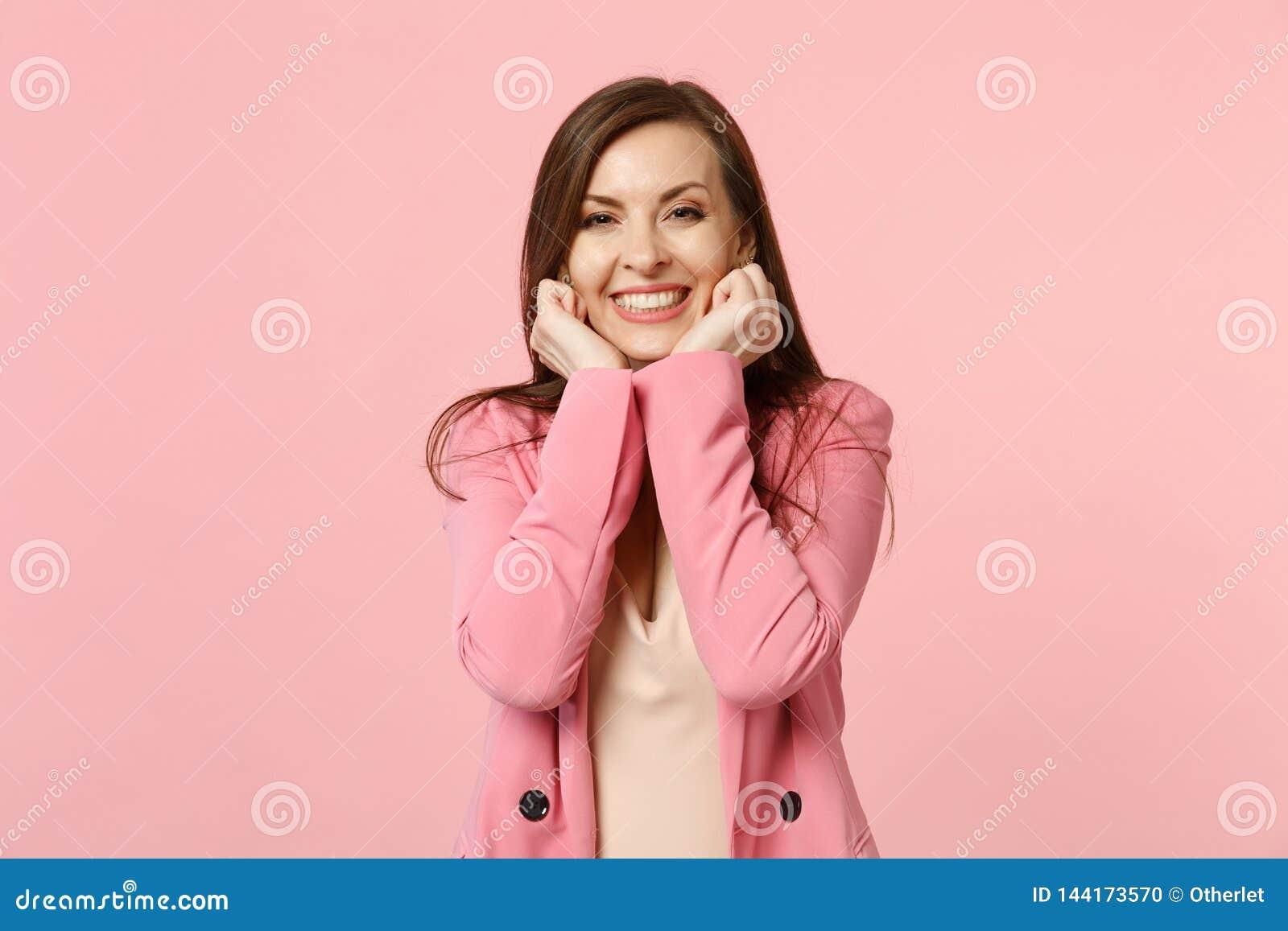 Αρκετά χαμογελώντας γοητευτική νέα γυναίκα που φορά το σακάκι που σφίγγει τις πυγμές εκμετάλλευσης κοντά στα μάγουλα στο ρόδινο τ