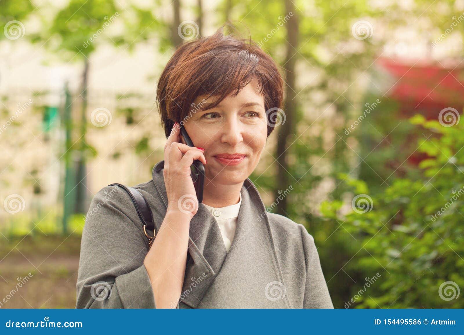 Αρκετά ώριμο τηλέφωνο γυναικών, υπαίθρια πορτρέτο
