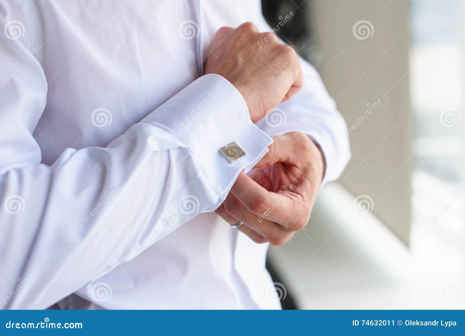 eafbac53ecdb Αρσενικά μανικετόκουμπα κουμπιών Ο επιχειρηματίας κουμπώνει τα  μανικετόκουμπα στο άσπρο πουκάμισο Ο νεόνυμφος το πρωί φορά το πουκάμισο σε  έναν γάμο