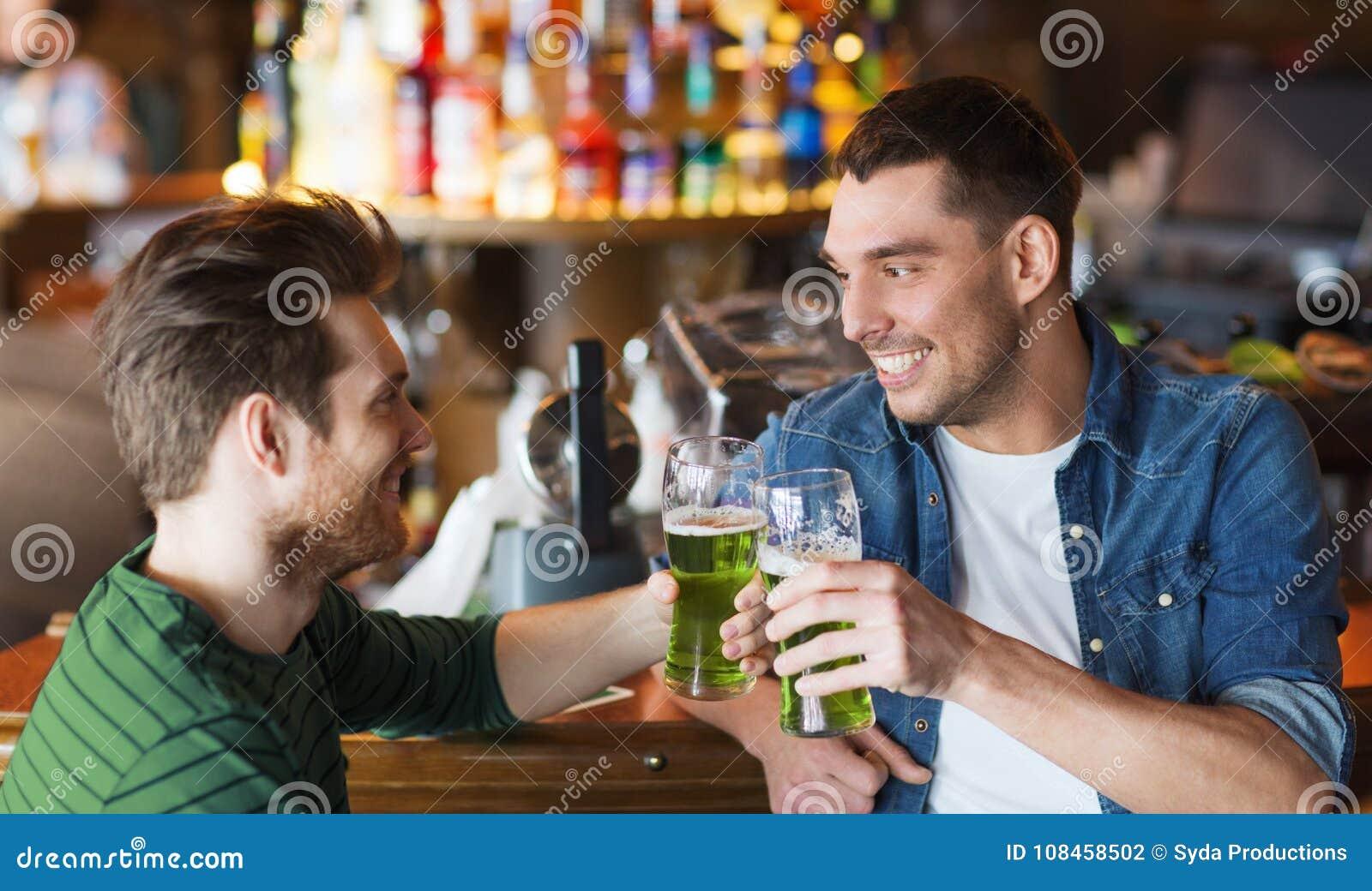 Αρσενικοί φίλοι που πίνουν την πράσινη μπύρα στο φραγμό ή το μπαρ