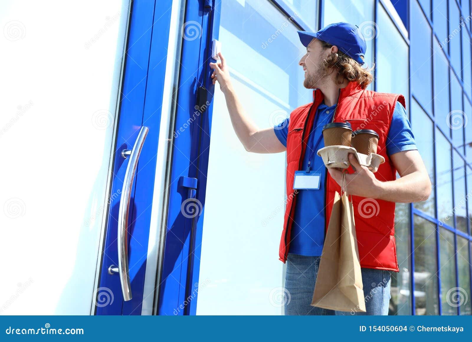 Αρσενικός αγγελιαφόρος με τη διαταγή που χτυπά στο doorbell στην είσοδο i