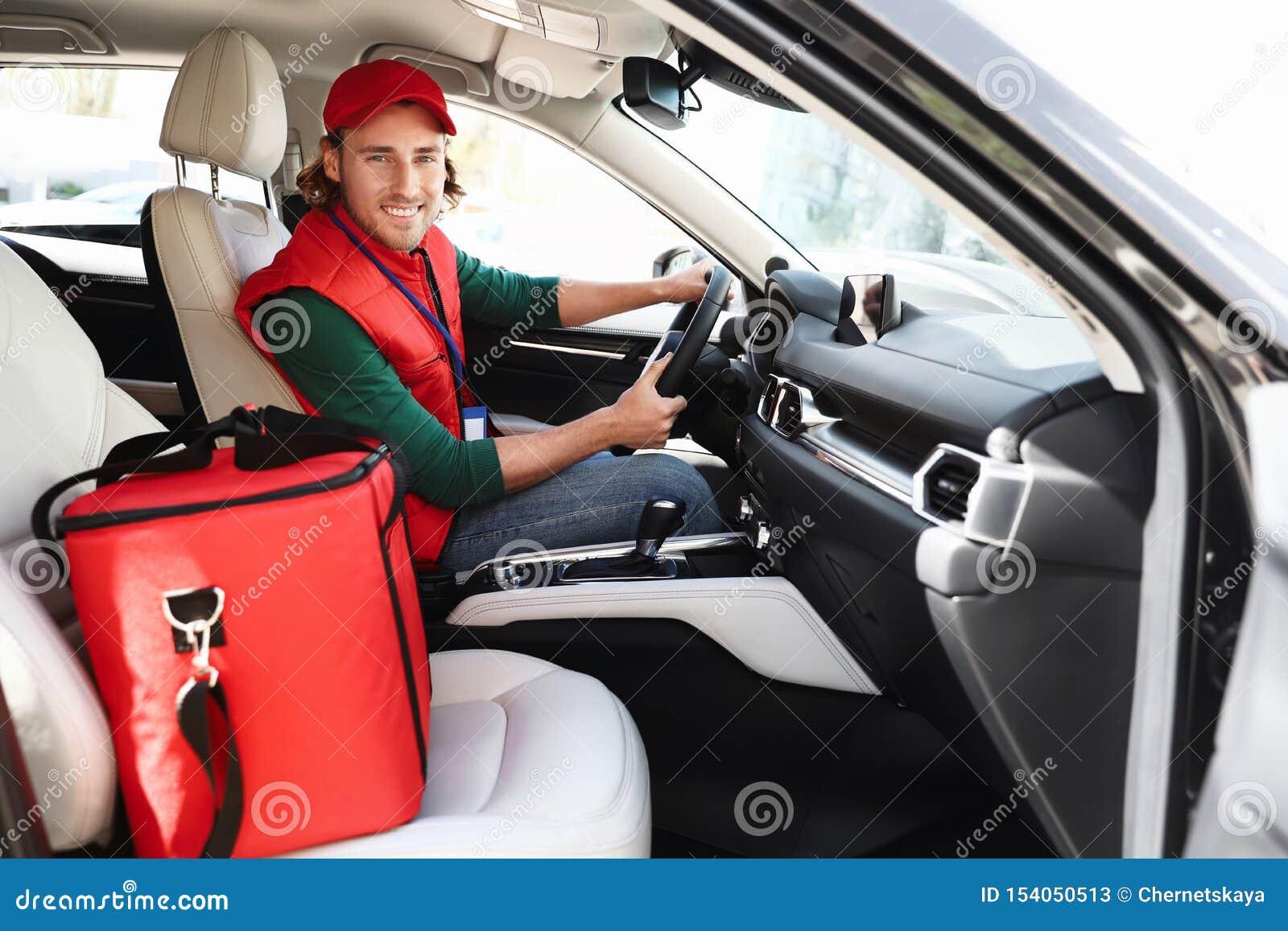 Αρσενικός αγγελιαφόρος με τη θερμο τσάντα στο αυτοκίνητο i