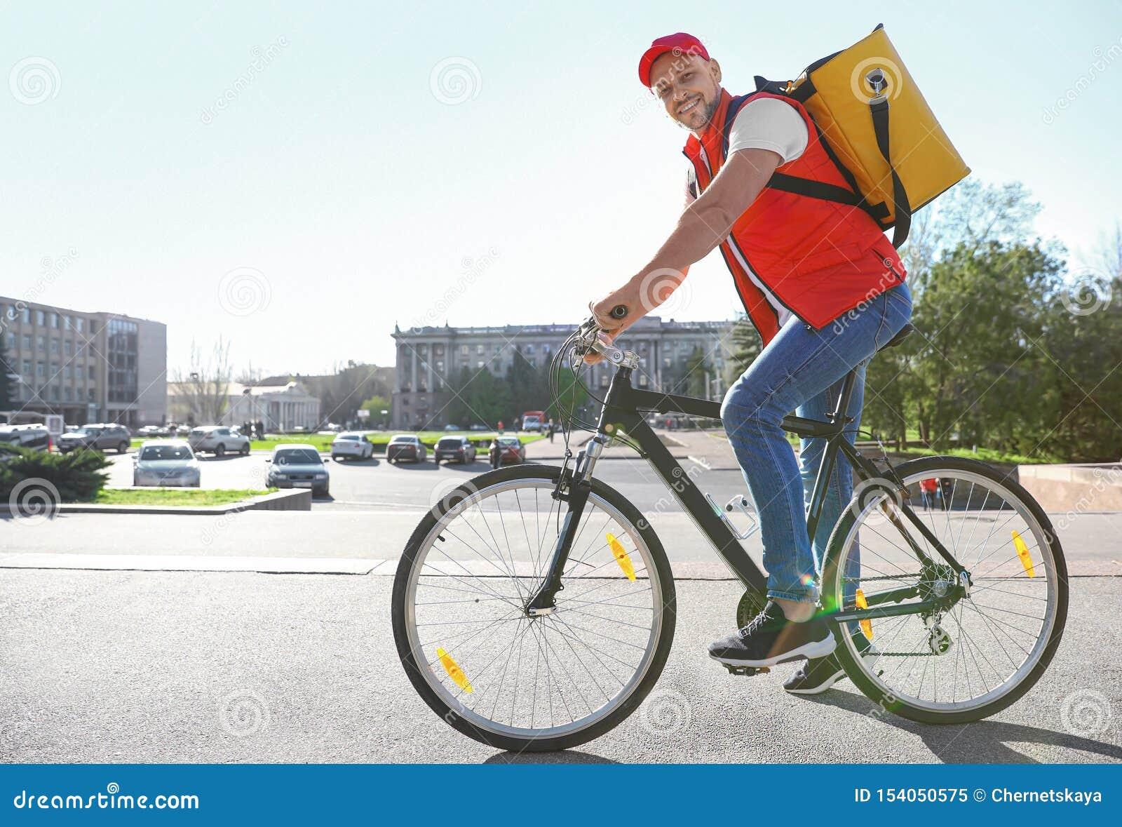 Αρσενικός αγγελιαφόρος στο ποδήλατο που παραδίδει τα τρόφιμα