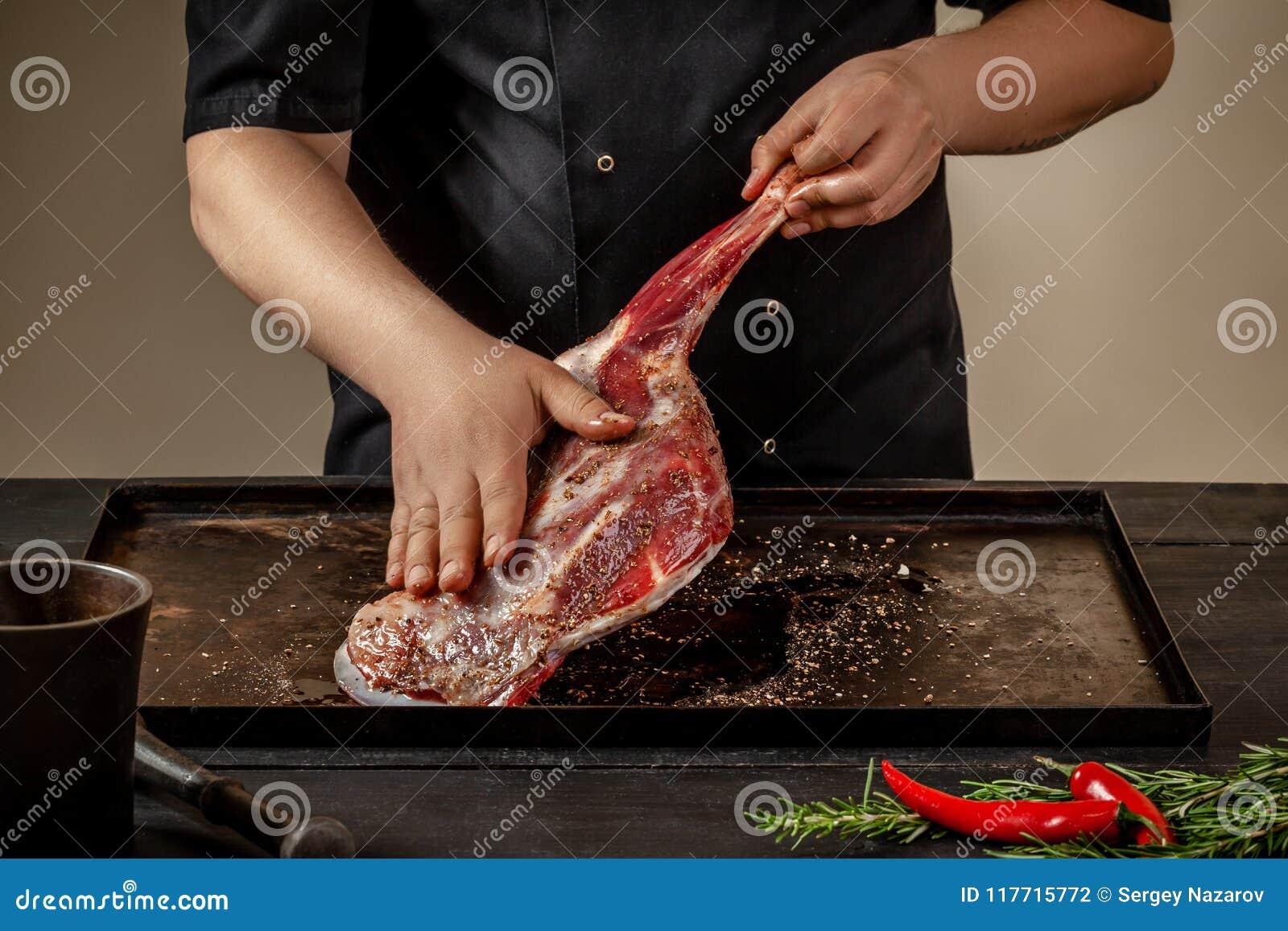 Αρσενικός αρχιμάγειρας που τρίβει τις ακατέργαστες κνήμες αρνιών με το αλάτι και το πιπέρι στο δίσκο πετρών στον ξύλινο πίνακα Αρ