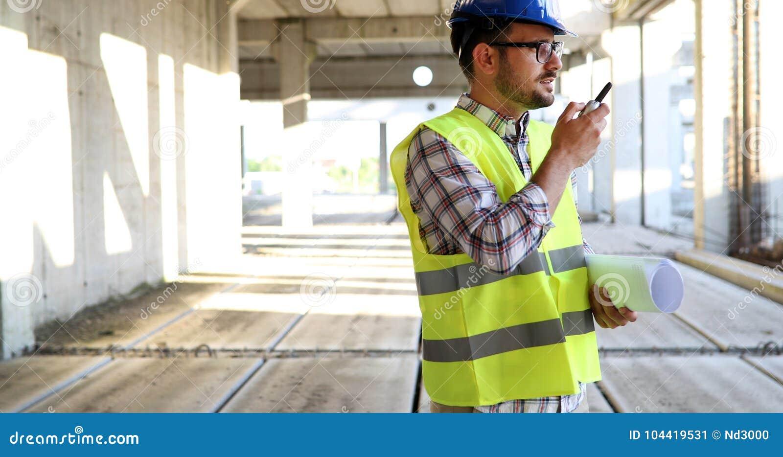Αρσενικός αρχιτέκτονας με τα σχεδιαγράμματα που χρησιμοποιούν walkie-talkie