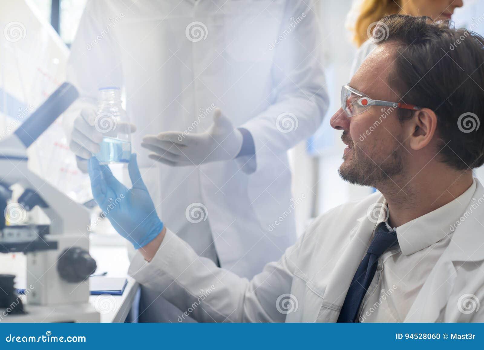 Αρσενικός επιστήμονας που συνεργάζεται με το μικροσκόπιο, την ομάδα στο εργαστήριο που κάνει την έρευνα, τον άνδρα και τη γυναίκα