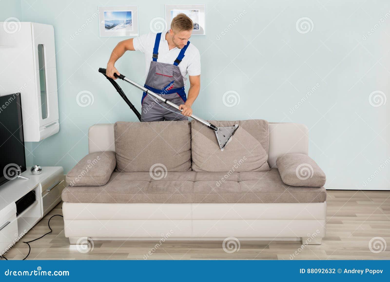 Αρσενικός καθαρίζοντας καναπές εργαζομένων με την ηλεκτρική σκούπα