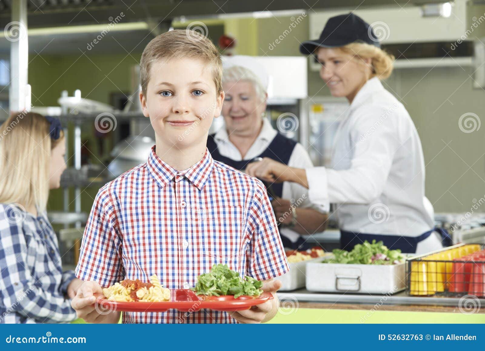 Αρσενικός μαθητής με το υγιές μεσημεριανό γεύμα στη σχολική καφετέρια
