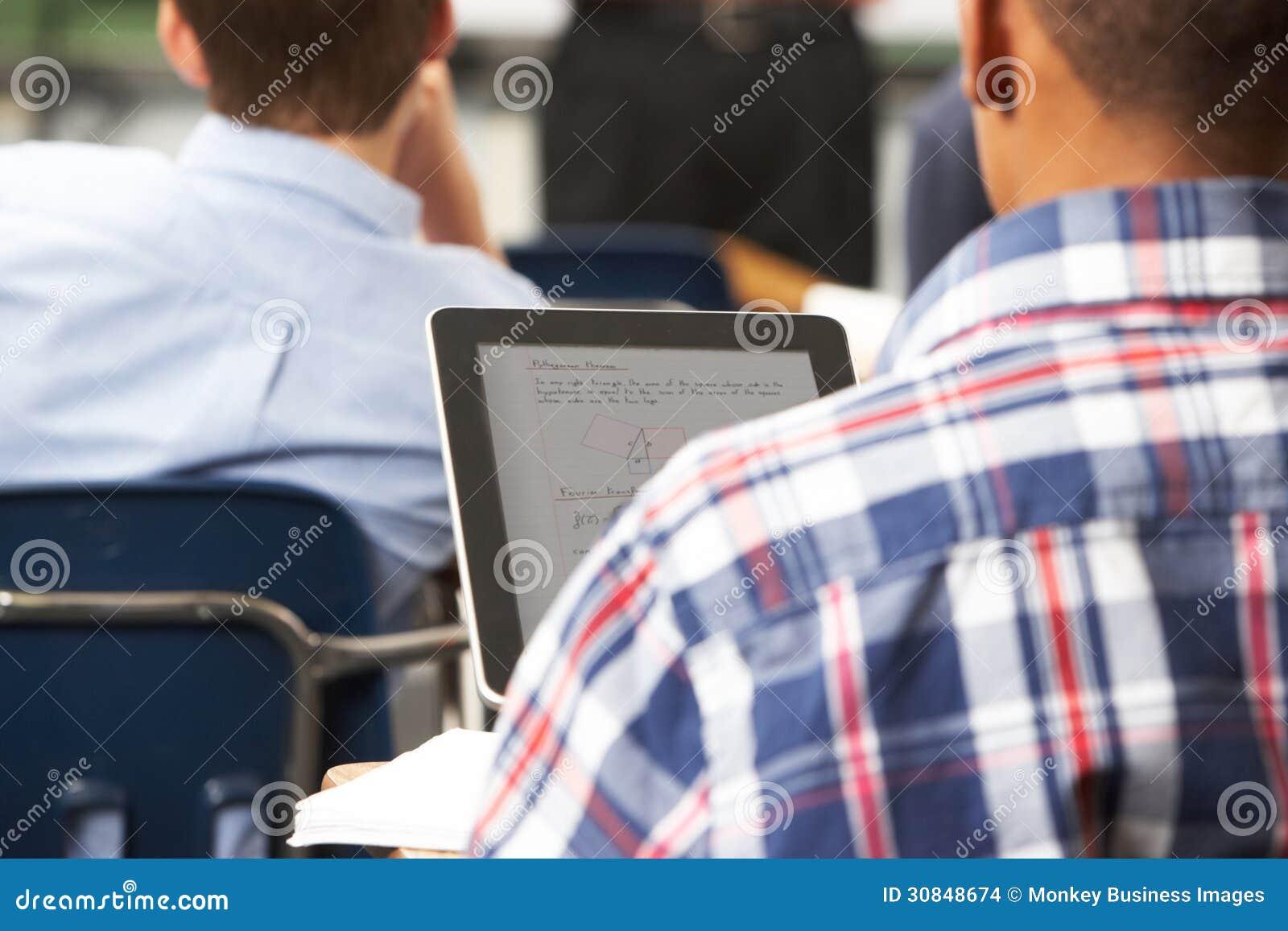 Αρσενικός μαθητής που χρησιμοποιεί την ψηφιακή ταμπλέτα στην τάξη