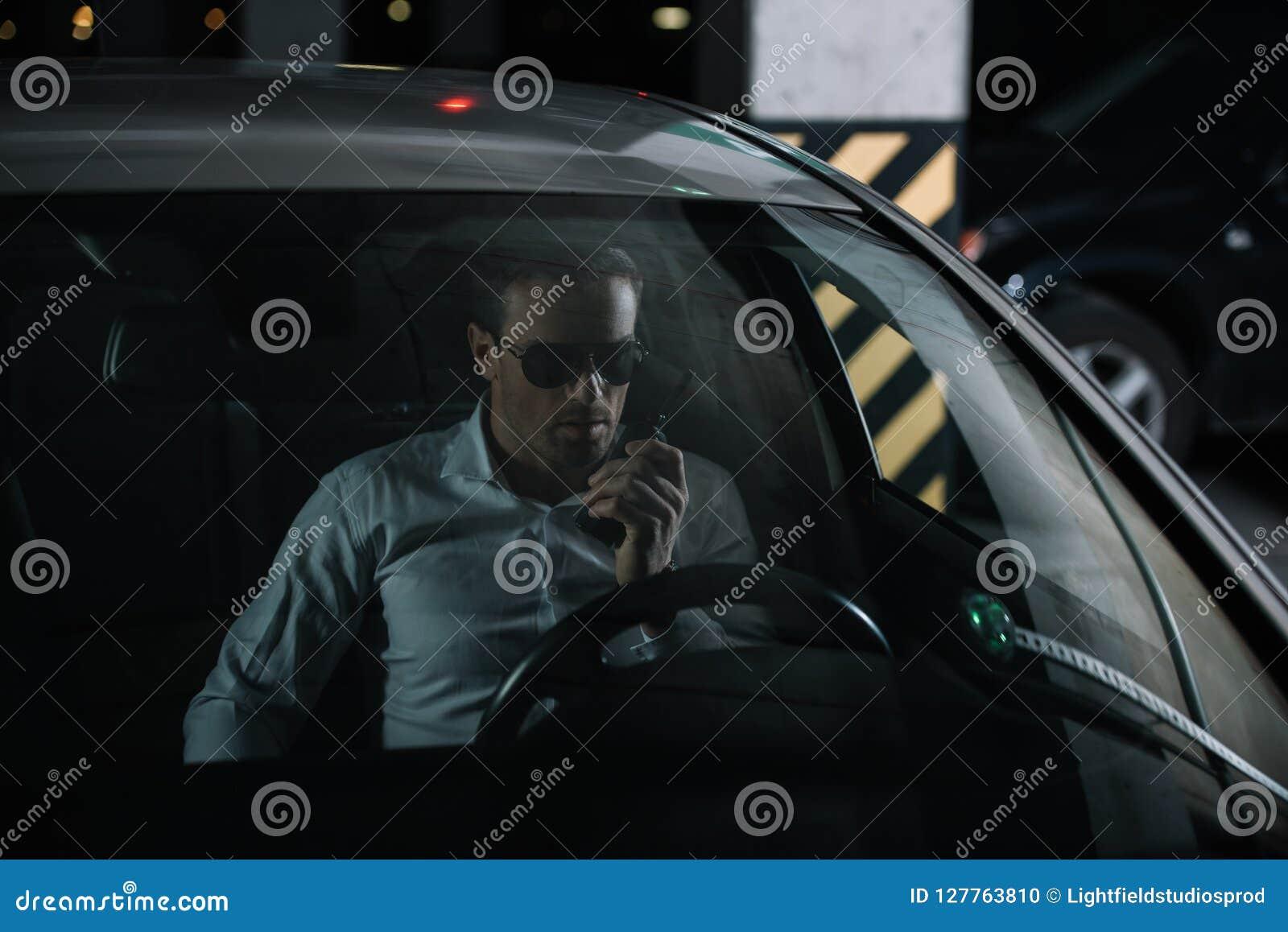 αρσενικός μυστικός αξιωματούχος στα γυαλιά ηλίου χρησιμοποιώντας την ομιλούσα ταινία walkie και καθμένος