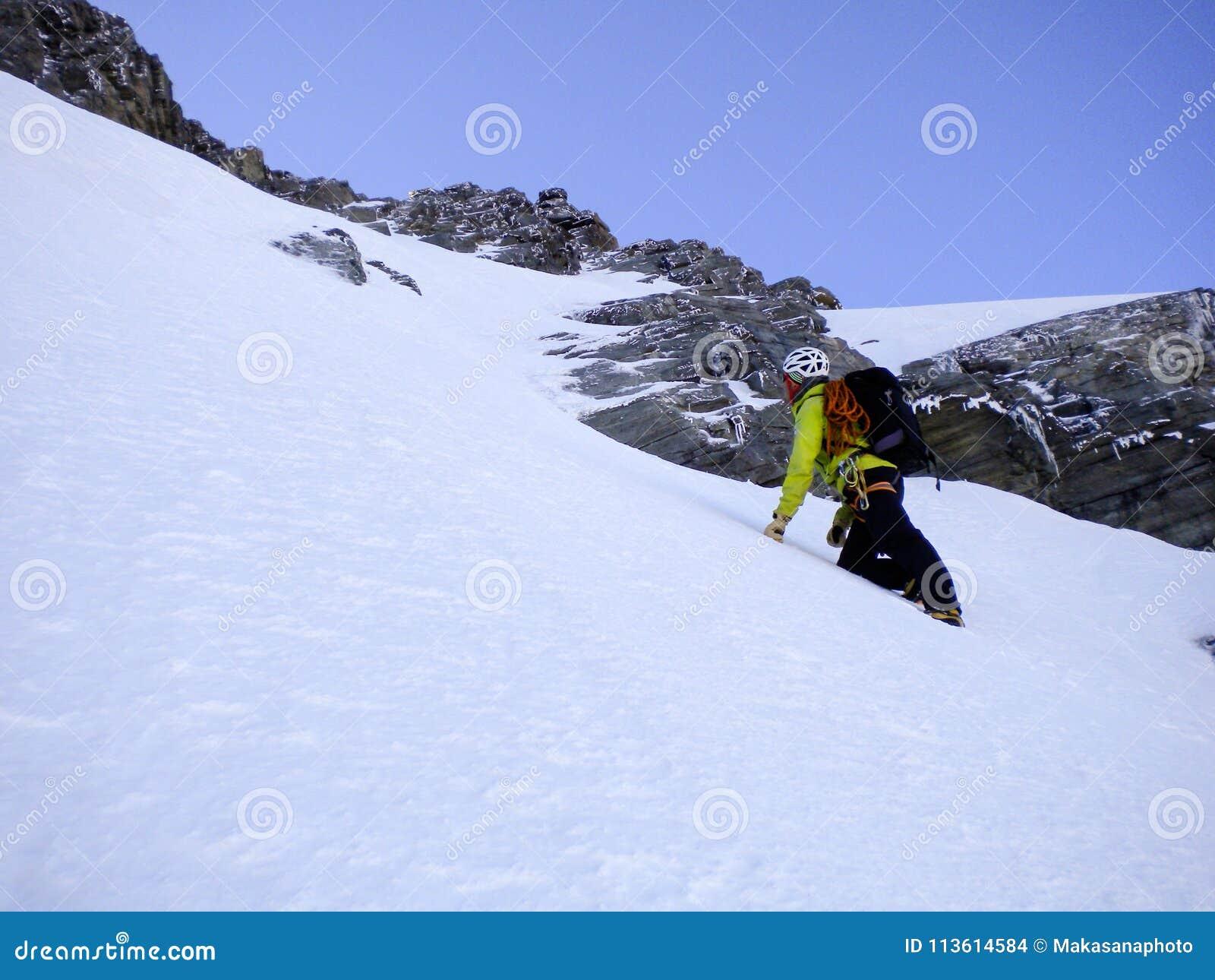 Αρσενικός οδηγός βουνών που αναρριχείται σε ένα απότομο χιόνι couloir στο δρόμο του σε μια υψηλή κορυφή στις ελβετικές Άλπεις