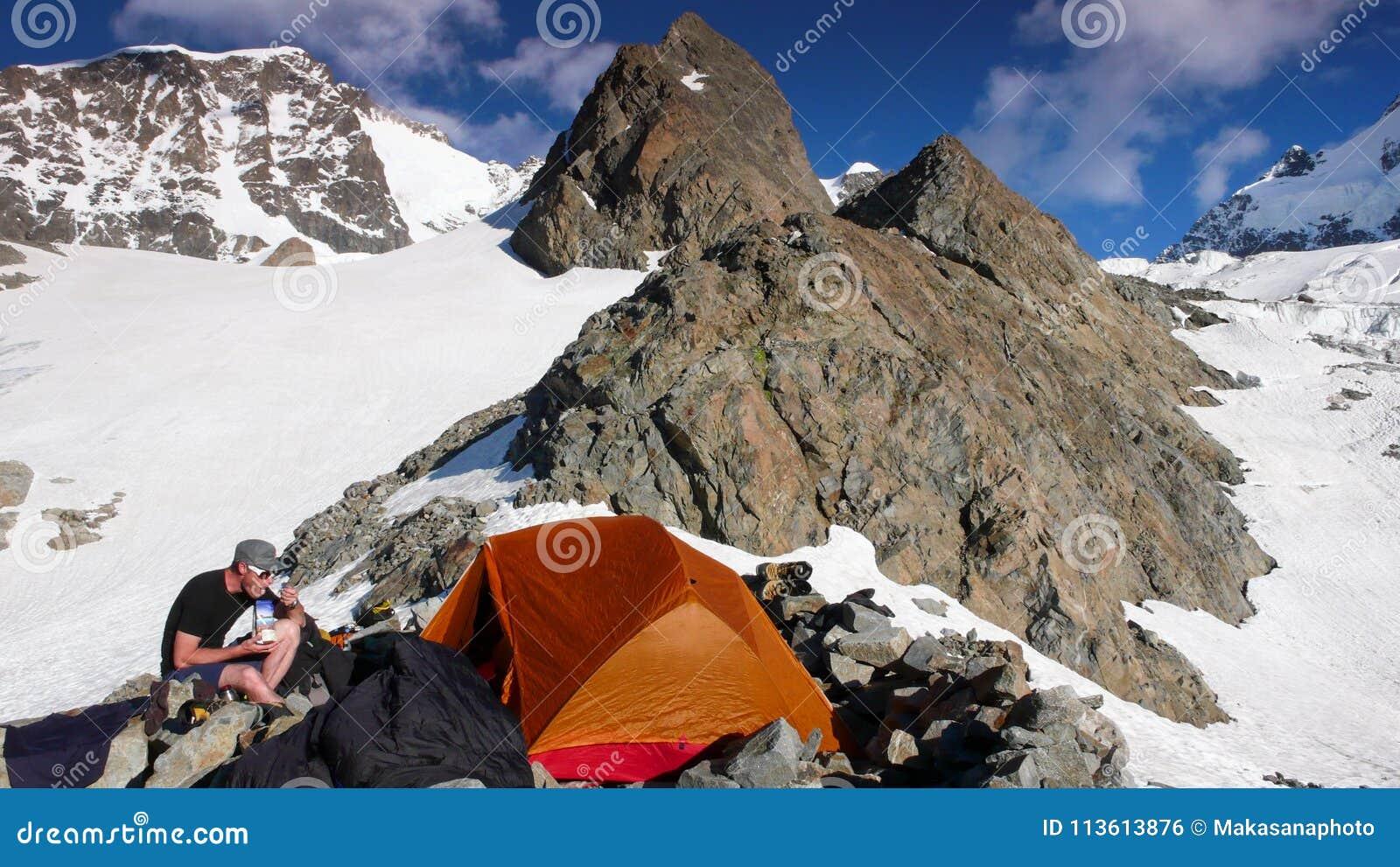 Αρσενικός ορειβάτης βουνών που τρώει στο στρατόπεδο βάσεων από μια πορτοκαλιά σκηνή με ένα θεαματικό τοπίο βουνών γύρω από τον