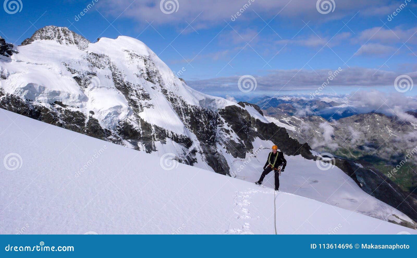 Αρσενικός ορειβάτης βουνών σε έναν υψηλό αλπικό παγετώνα με μια μεγάλη άποψη του φανταστικού τοπίου βουνών πίσω από τον