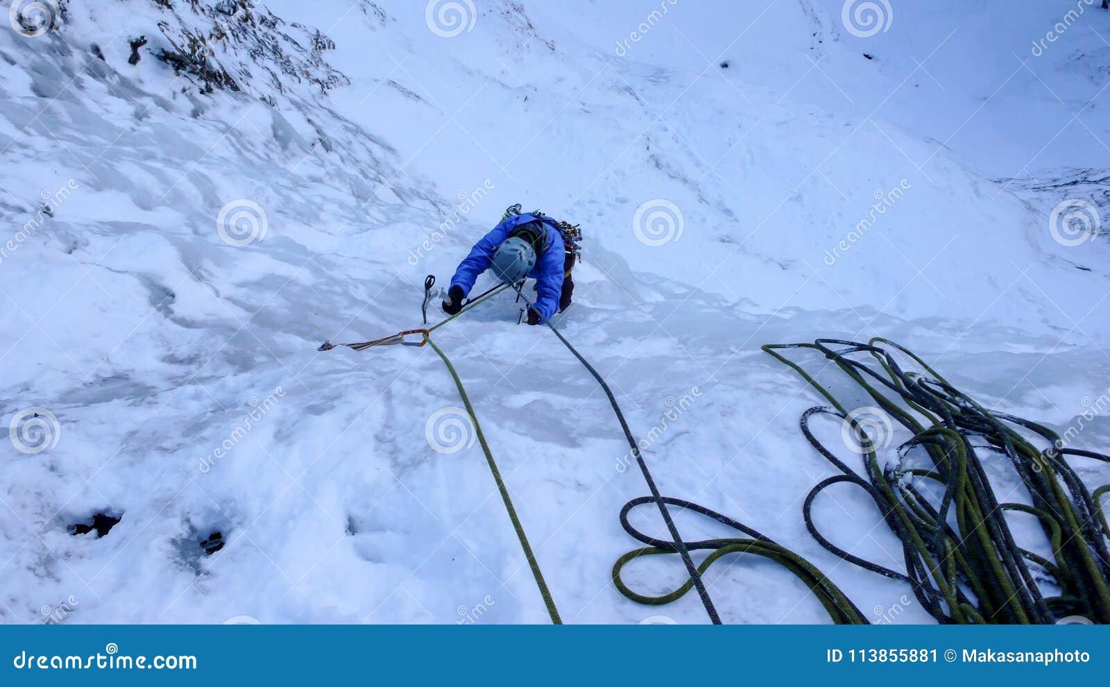 Αρσενικός ορειβάτης πάγου σε μια μπλε ζακέτα σε έναν απότομο παγωμένο καταρράκτη το βαθύ χειμώνα στις Άλπεις της Ελβετίας