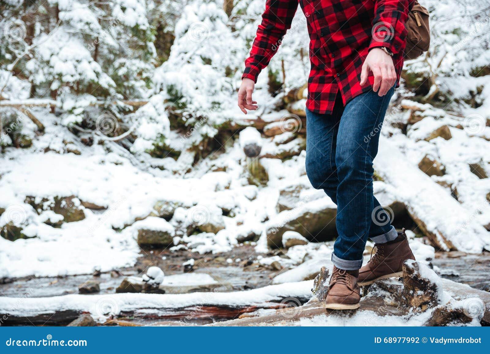 Αρσενικός οδοιπόρος που περπατά στον ποταμό βουνών
