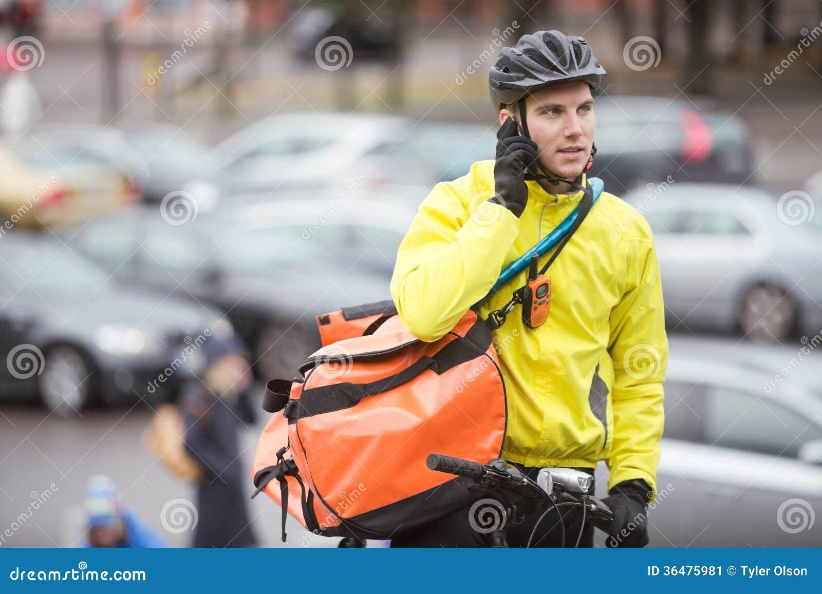 Αρσενικός ποδηλάτης με την τσάντα αγγελιαφόρων που χρησιμοποιεί το κινητό τηλέφωνο