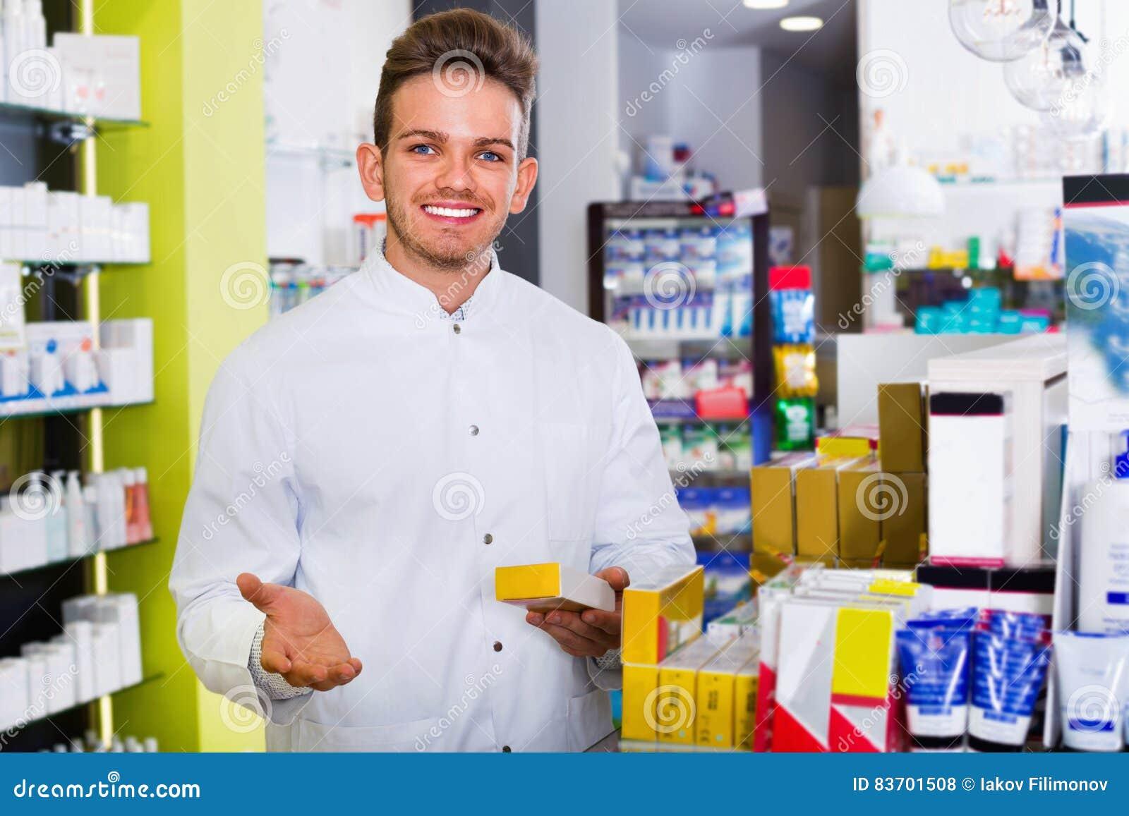 Αρσενικός φαρμακοποιός που φορά το άσπρο παλτό που στέκεται στο φαρμακείο