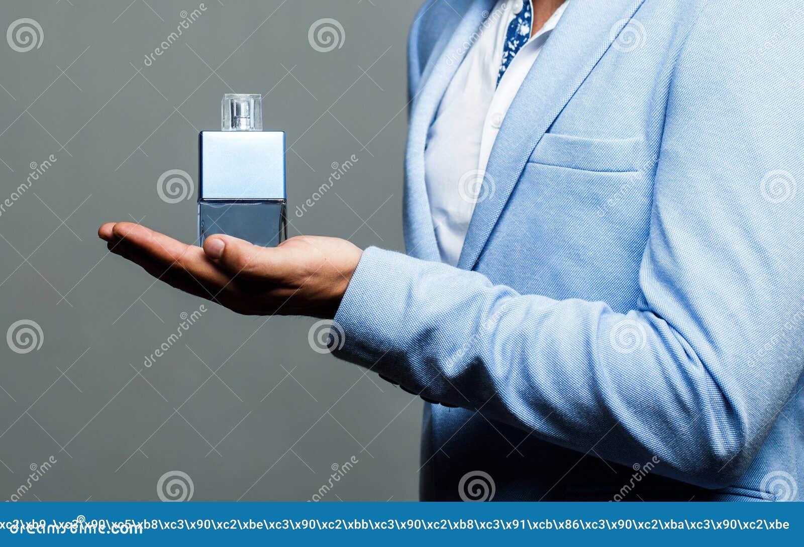 Αρσενικό άρωμα, γενειοφόρο άτομο σε ένα κοστούμι Άρωμα ατόμων, άρωμα Αρσενικό να κρατήσει ψηλά μπουκάλι του αρώματος Άρωμα ή Κολω