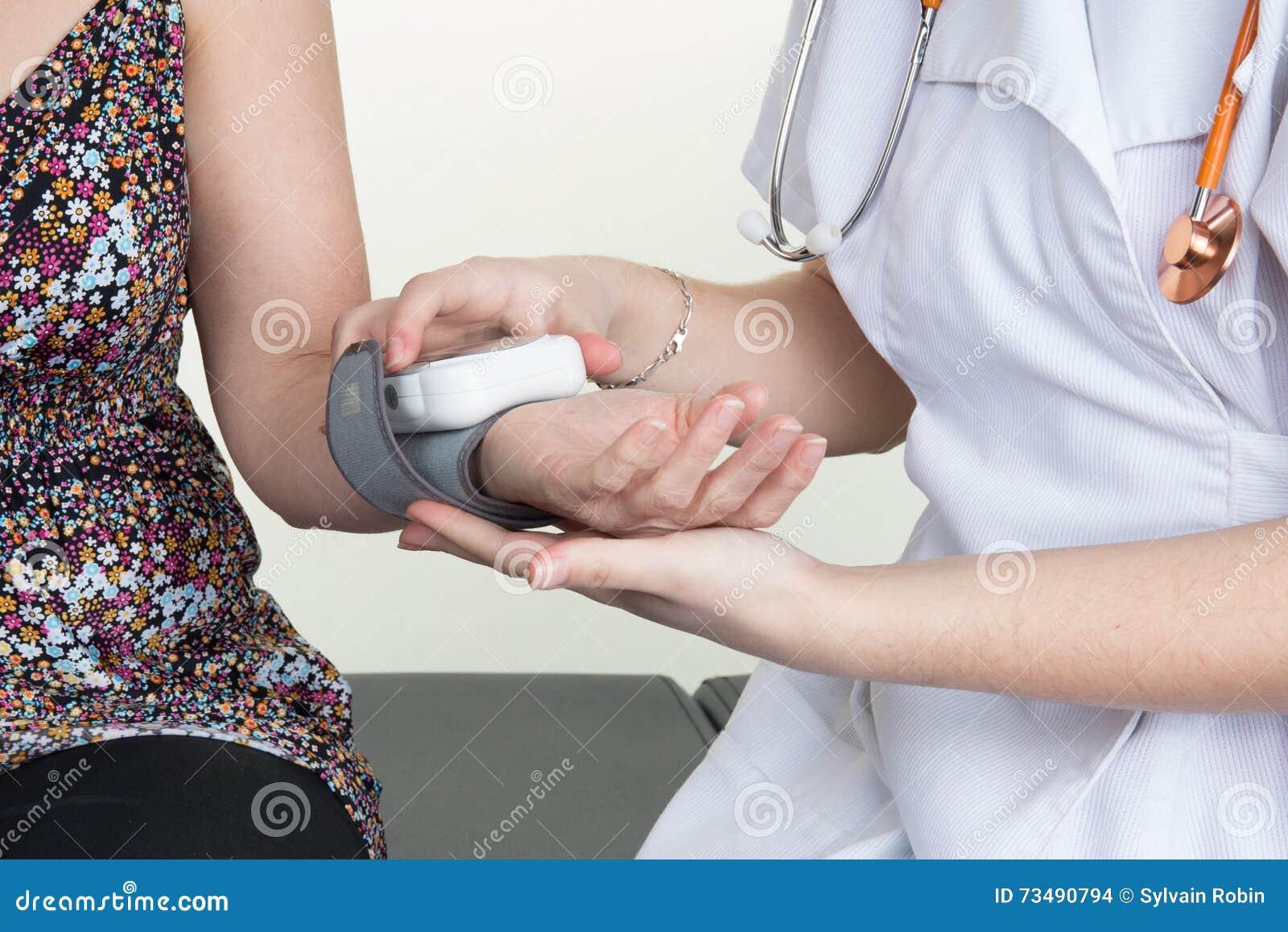 Αρσενικό νοσοκόμα ή γιατρός που παίρνει μια ανάγνωση πίεσης του αίματος που χρησιμοποιεί μια μανσέτα σε μια γυναίκα