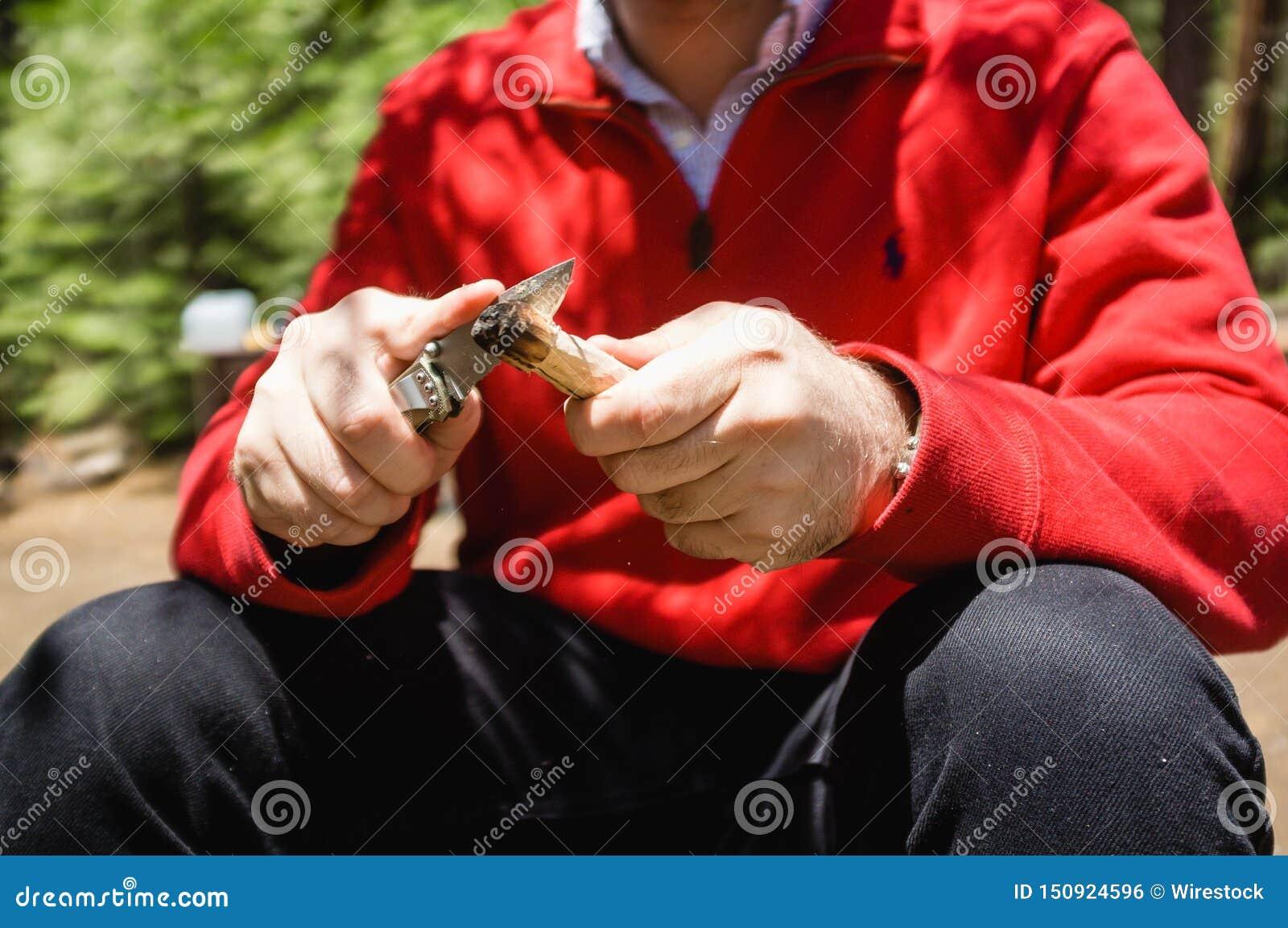 Αρσενικό σε ένα κόκκινο σακάκι που ακονίζει το μαχαίρι του στις άγρια περιοχές