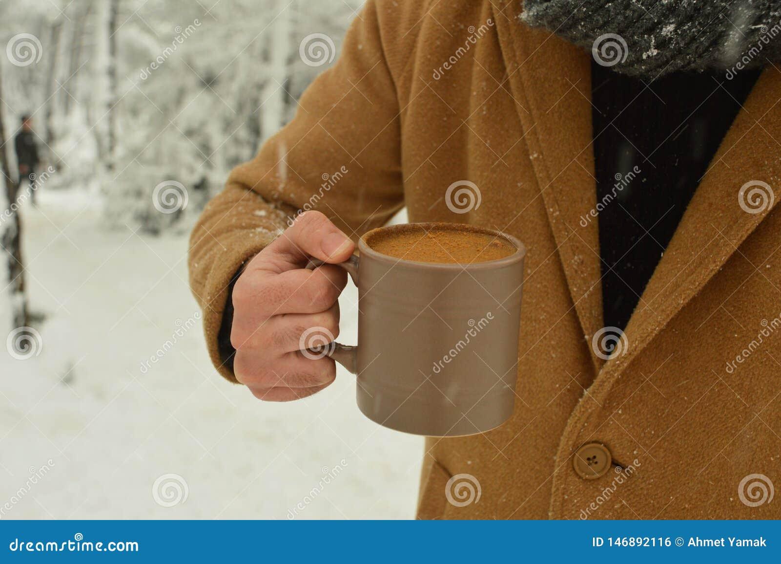 Αρσενικό φλιτζάνι του καφέ εκμετάλλευσης χεριών με το χιονώδες υπόβαθρο
