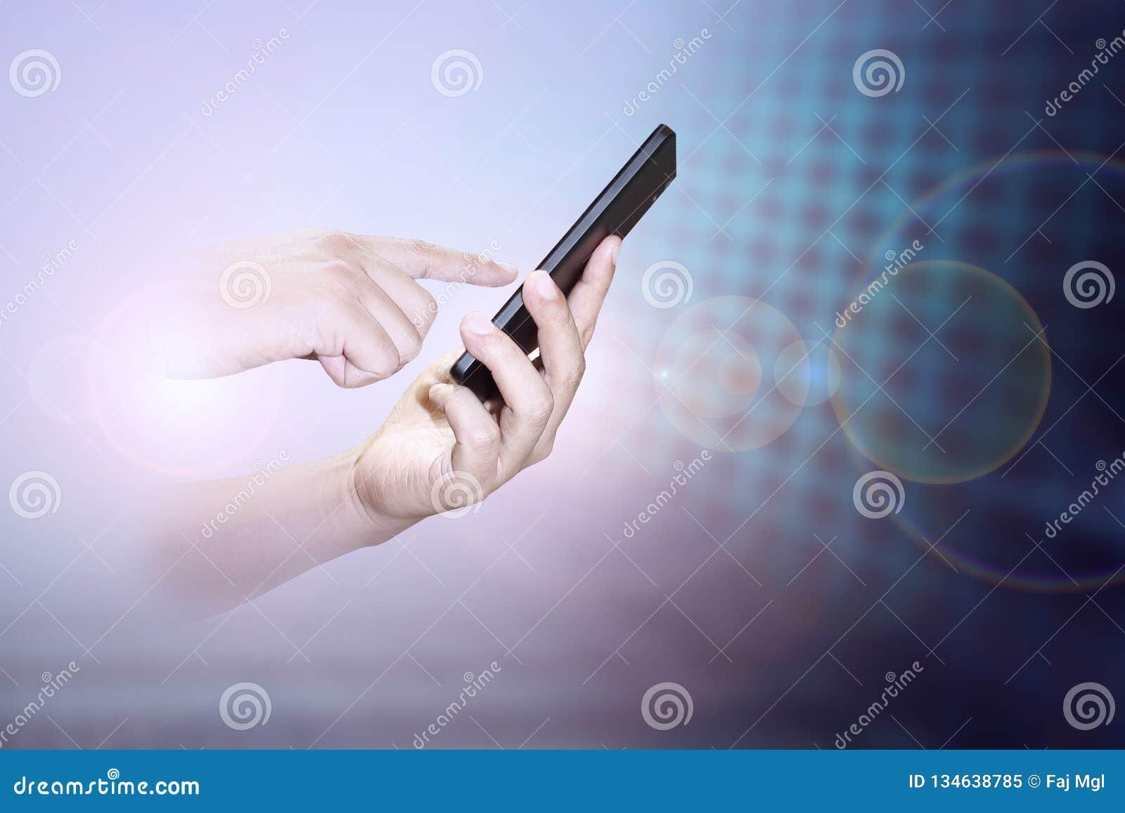 Αρσενικό χέρι που χρησιμοποιεί το κινητό τηλέφωνο