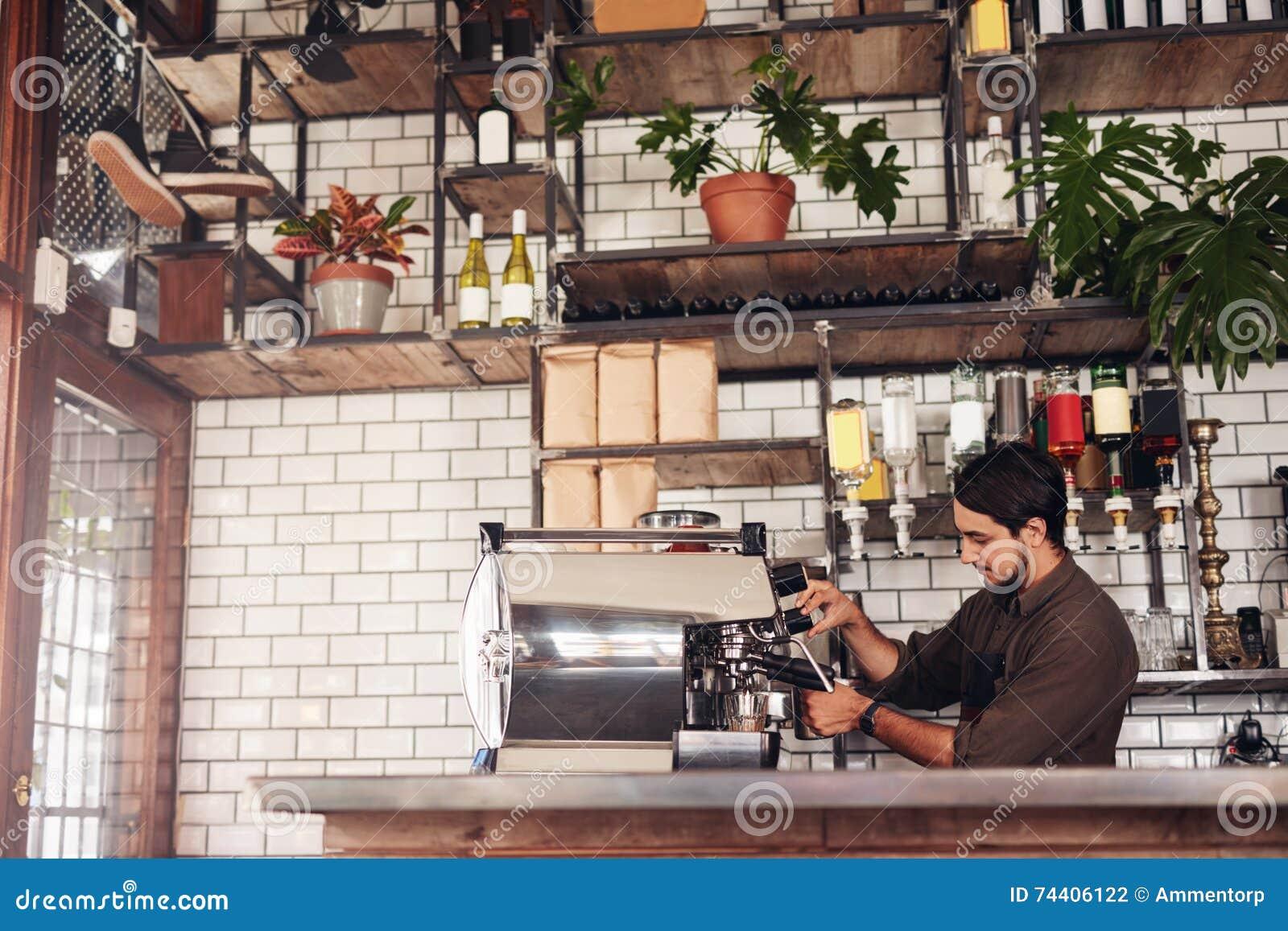 Αρσενικό barista που κατασκευάζει ένα φλιτζάνι του καφέ