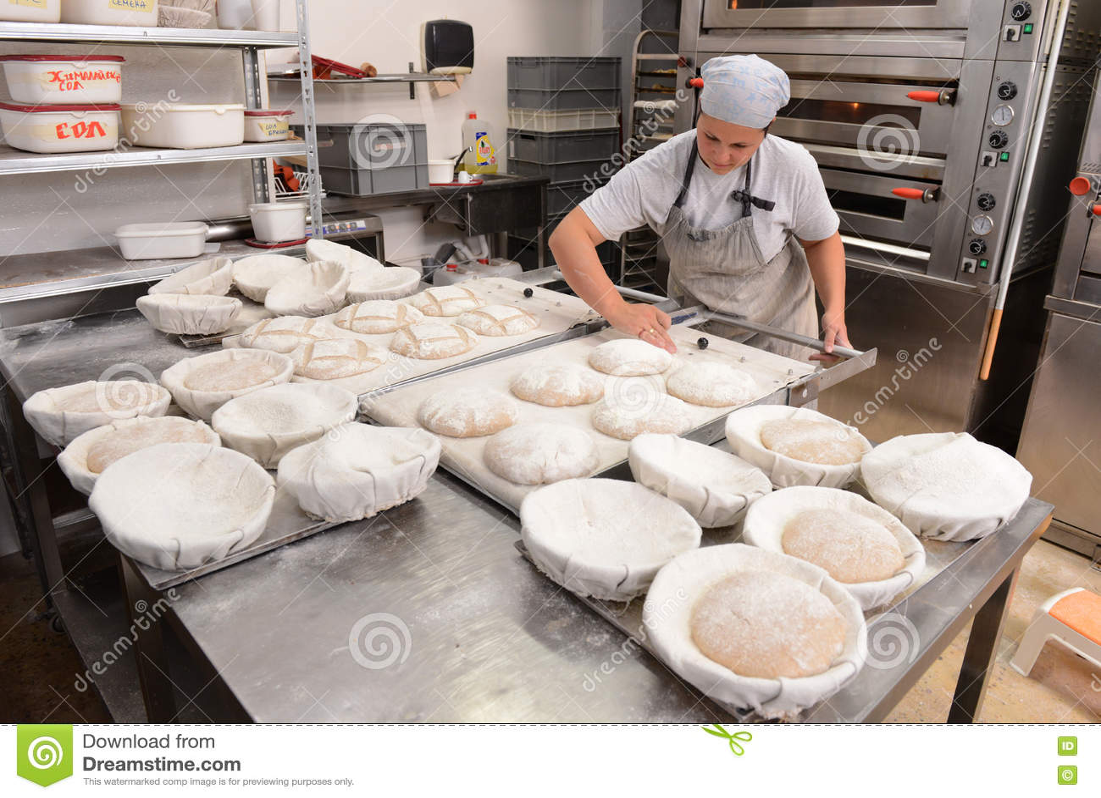 Αρτοποιοί που κατασκευάζουν τις χειροποίητες φραντζόλες του ψωμιού σε ένα οικογενειακό αρτοποιείο που διαμορφώνει τη ζύμη στις μο