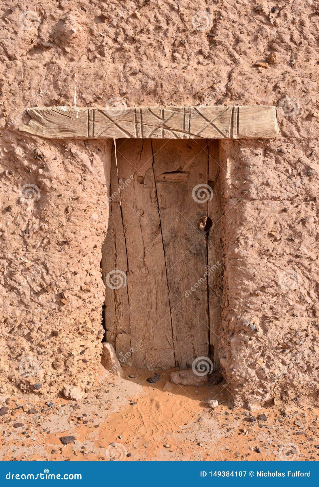 Αρχαία ξύλινη πόρτα του σπιτιού τούβλου λάσπης στο Σουδάν