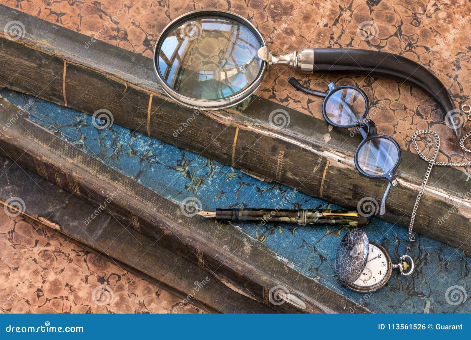 Αρχαία πολύτιμα βιβλία με πιό magnifier, τα γυαλιά, τη μάνδρα πηγών και το ρολόι τσεπών
