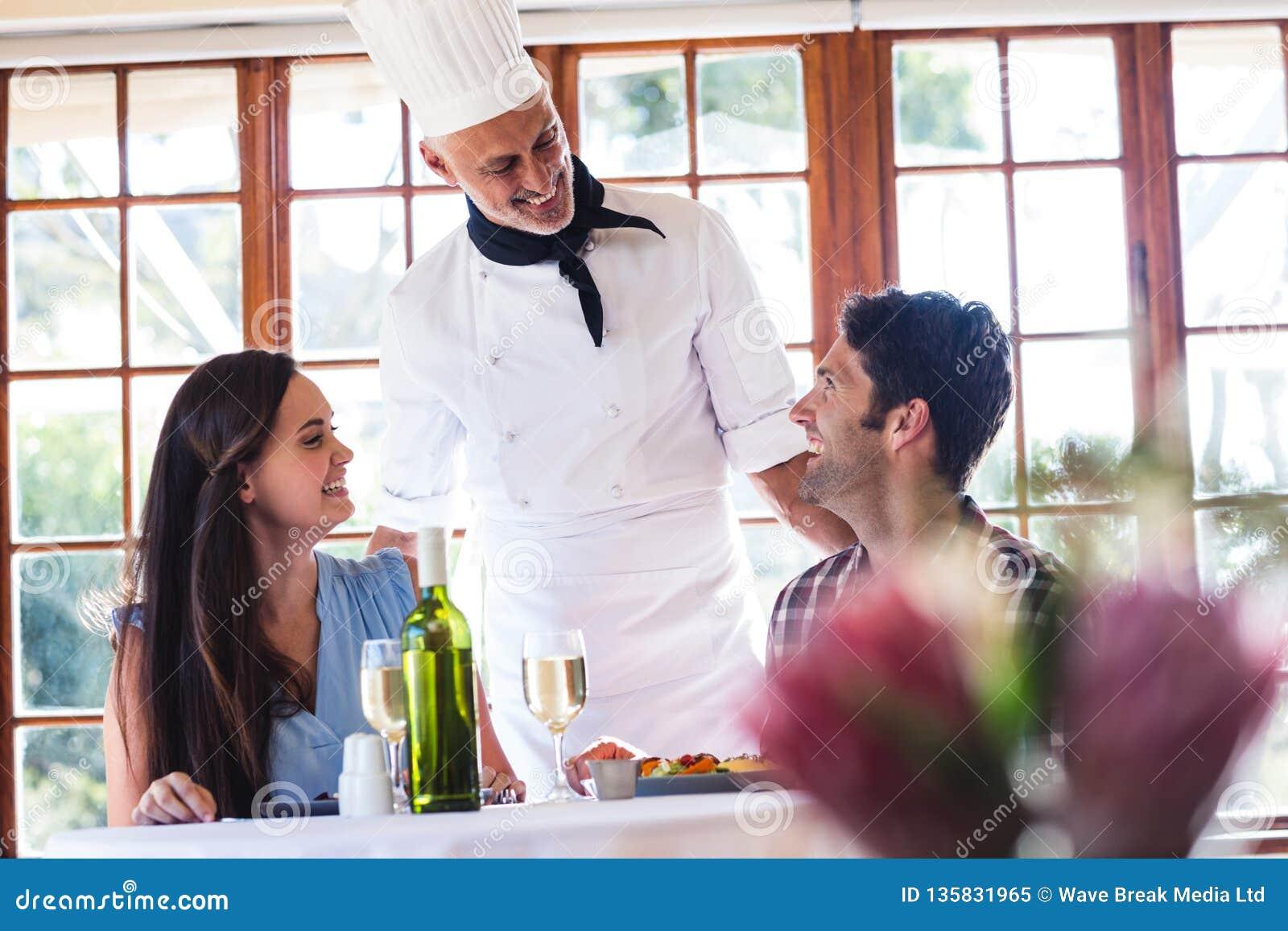 Αρχιμάγειρας που μιλά στο ζεύγος στο εστιατόριο
