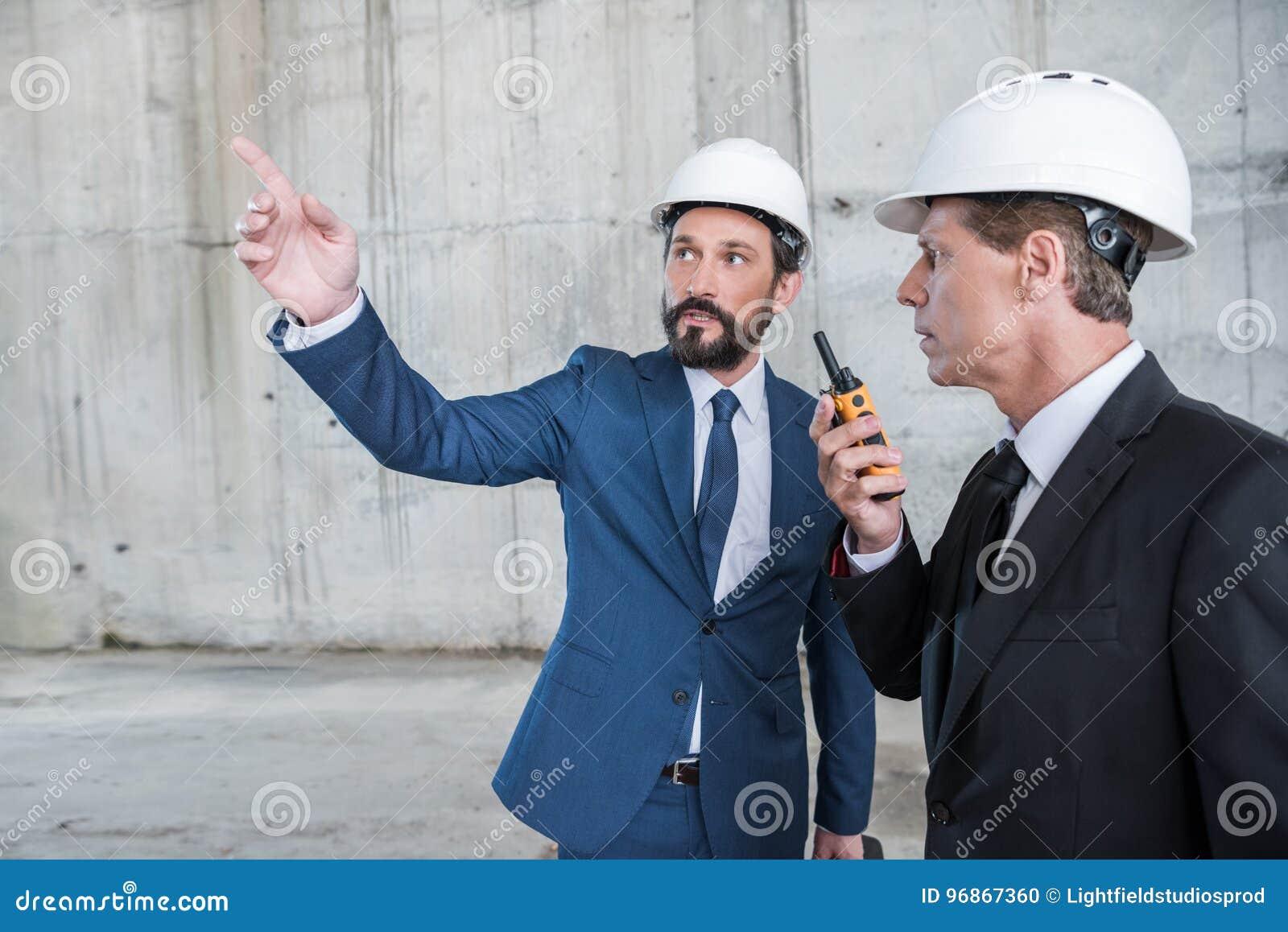 Αρχιτέκτονες hardhats χρησιμοποιώντας walkie-talkie και συζητώντας το πρόγραμμα στο εργοτάξιο οικοδομής