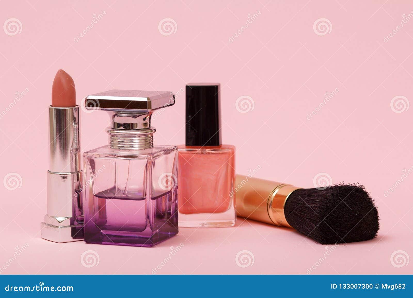 b4ea12098e2 Το άρωμα γυναικών, μπουκάλια με το καρφί γυαλίζει, βούρτσα και κραγιόν σε  ένα ρόδινο υπόβαθρο Καλλυντικά και αρώματα γυναικών
