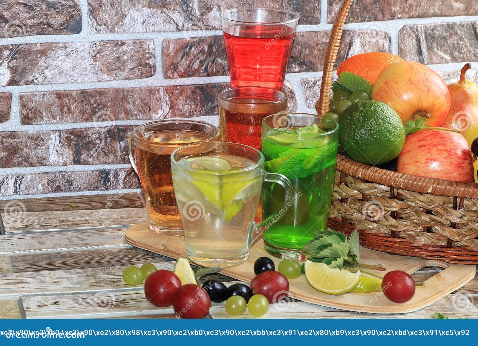 Ασβέστης goblets γυαλιού και φρούτα με τη μέντα σε έναν ξύλινο πίνακα