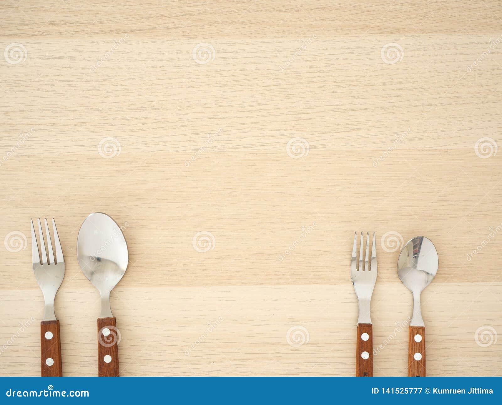 Ασημένια μαχαιροπήρουνα που τίθενται στον ξύλινο πίνακα