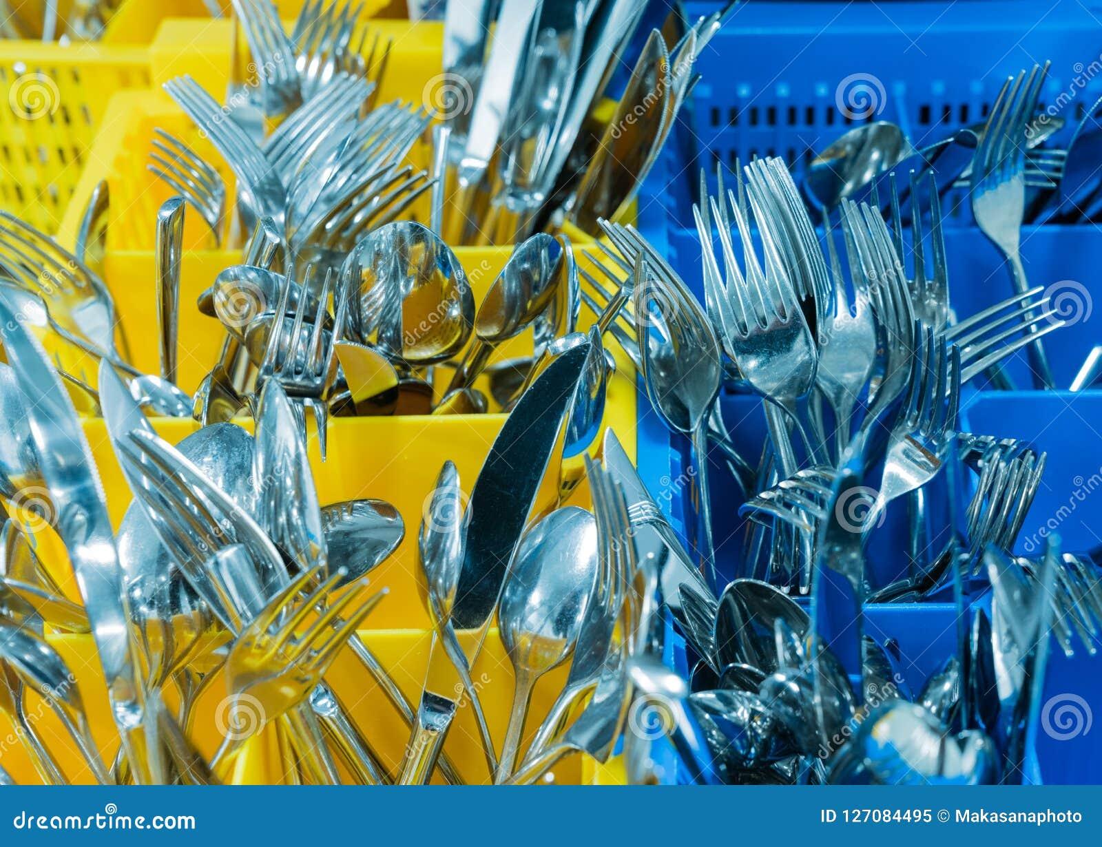 Ασημικές και μαχαιροπήρουνα στο ζωηρόχρωμο palstic ocntainer σε μια βιομηχανική κουζίνα εστιατορίων