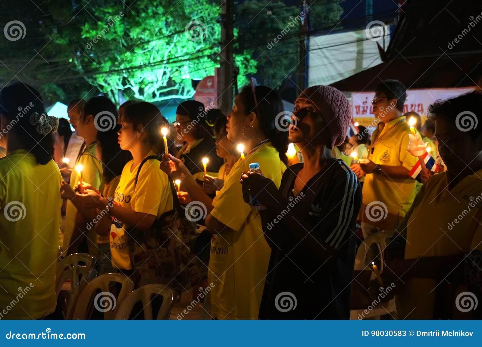 Ασιάτες στέκονται με τα κεριά Ταϊλανδοί προσεύχονται για την υγεία του βασιλιά