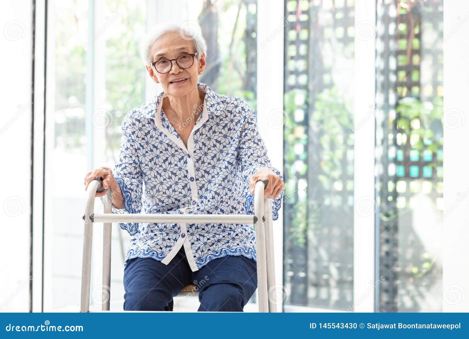 Ασιατική ανώτερη συνεδρίαση γυναικών με τον περιπατητή κατά τη διάρκεια της αποκατάστασης, ηλικιωμένα γυαλιά ένδυσης γυναικών, πο