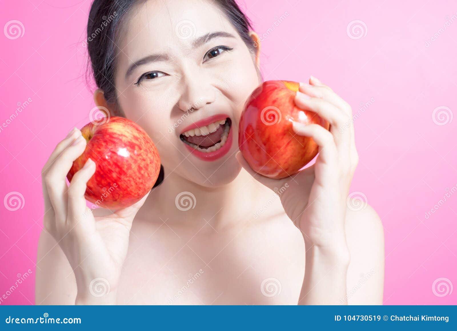 Ασιατική γυναίκα με την έννοια μήλων Αυτή που χαμογελά και που κρατά το μήλο Πρόσωπο ομορφιάς και φυσικό makeup Απομονωμένος πέρα