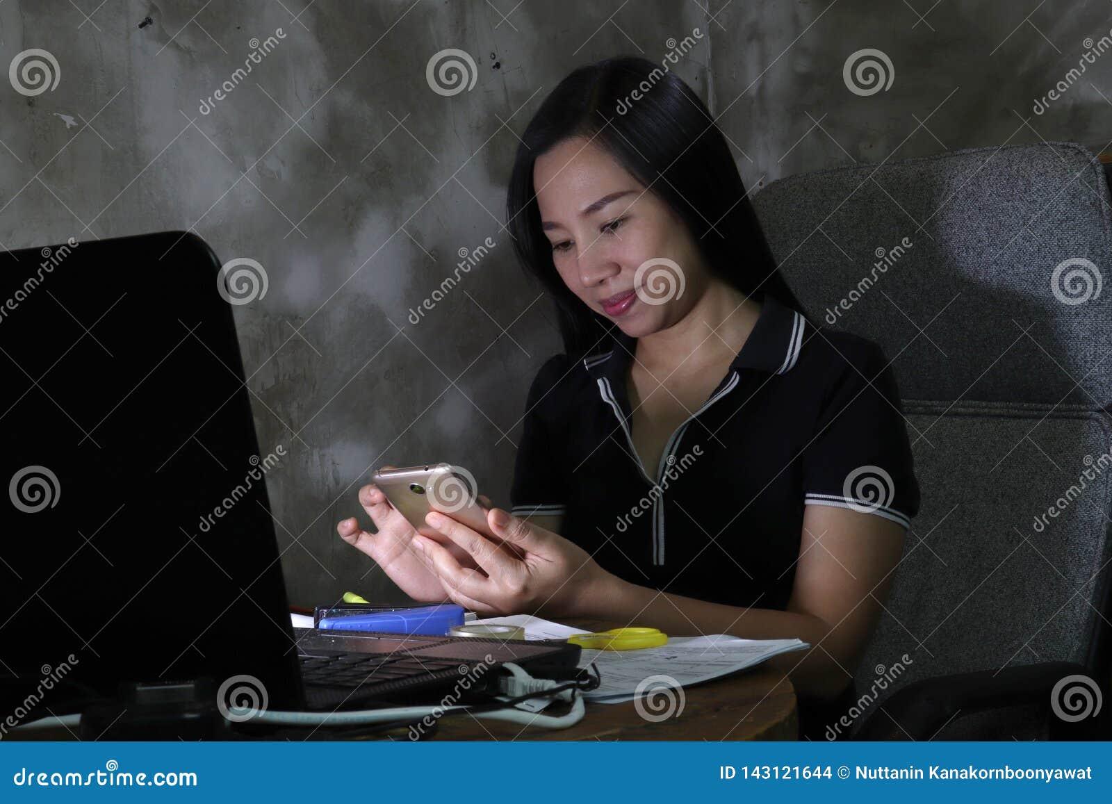 Ασιατική γυναίκα που εργάζεται από το σπίτι αργά στη νύχτα - εργαστείτε στη φτωχή έννοια φωτισμού το σκοτεινό φως έχει κάποιους σ