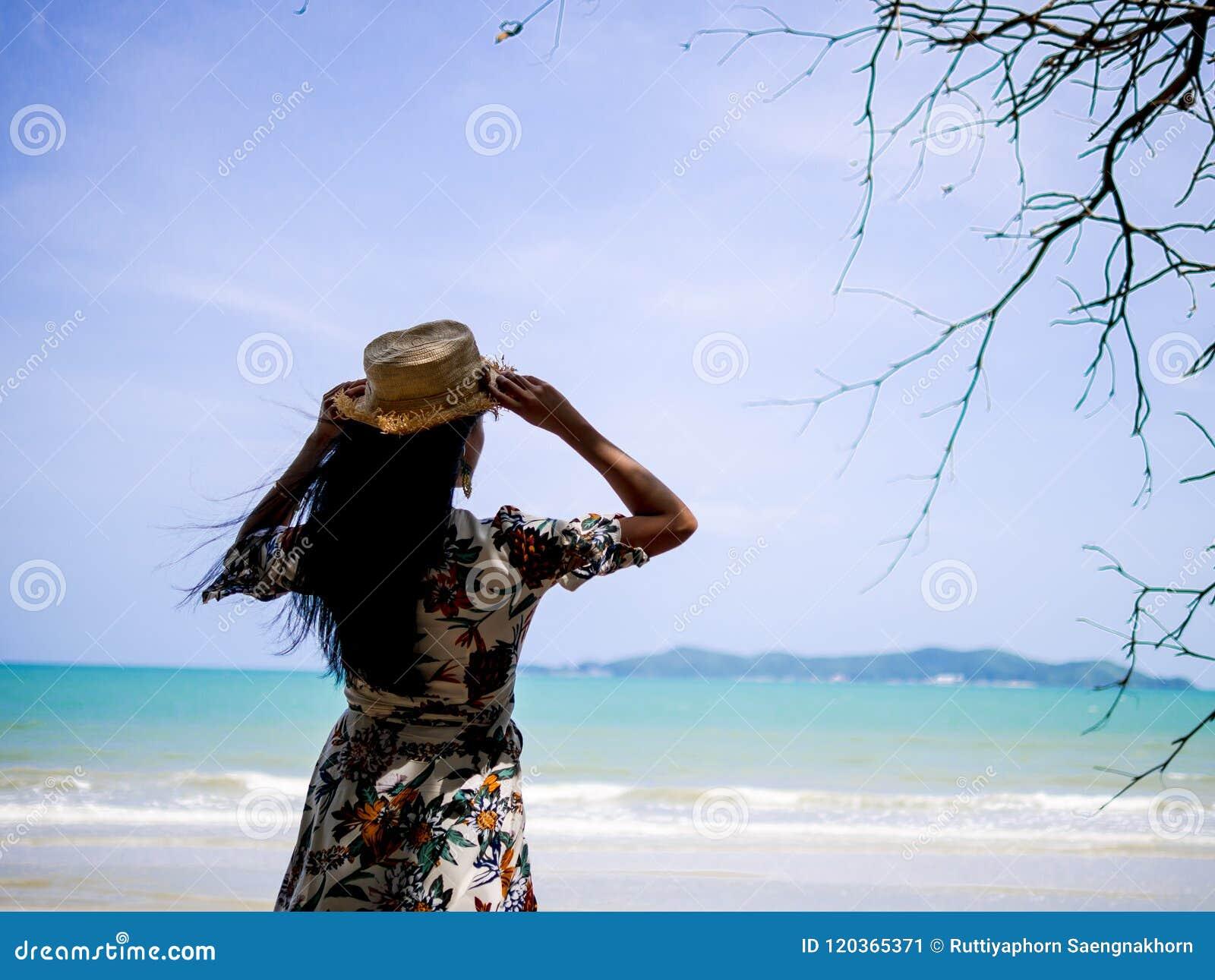 Ασιατική γυναίκα που φορά το Βοημίας ύφος φορεμάτων με το καπέλο που στέκεται στην ακτή που κοιτάζει στην άσπρα παραλία και το κύ