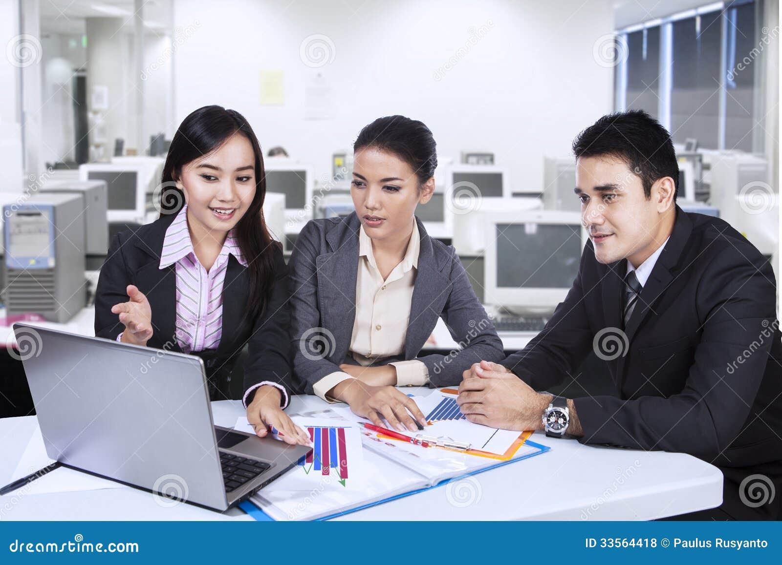 Ασιατική επιχειρησιακή τρία ομάδα με το lap-top στο γραφείο