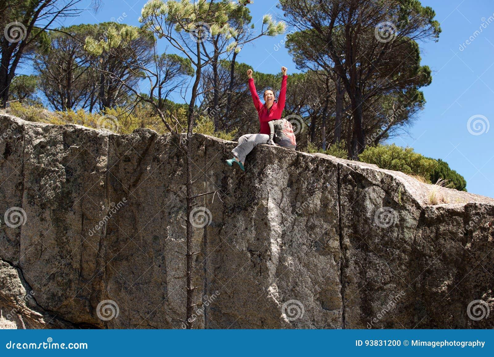 Ασιατική θηλυκή συνεδρίαση οδοιπόρων στην άκρη του βουνού με τα αυξημένα χέρια