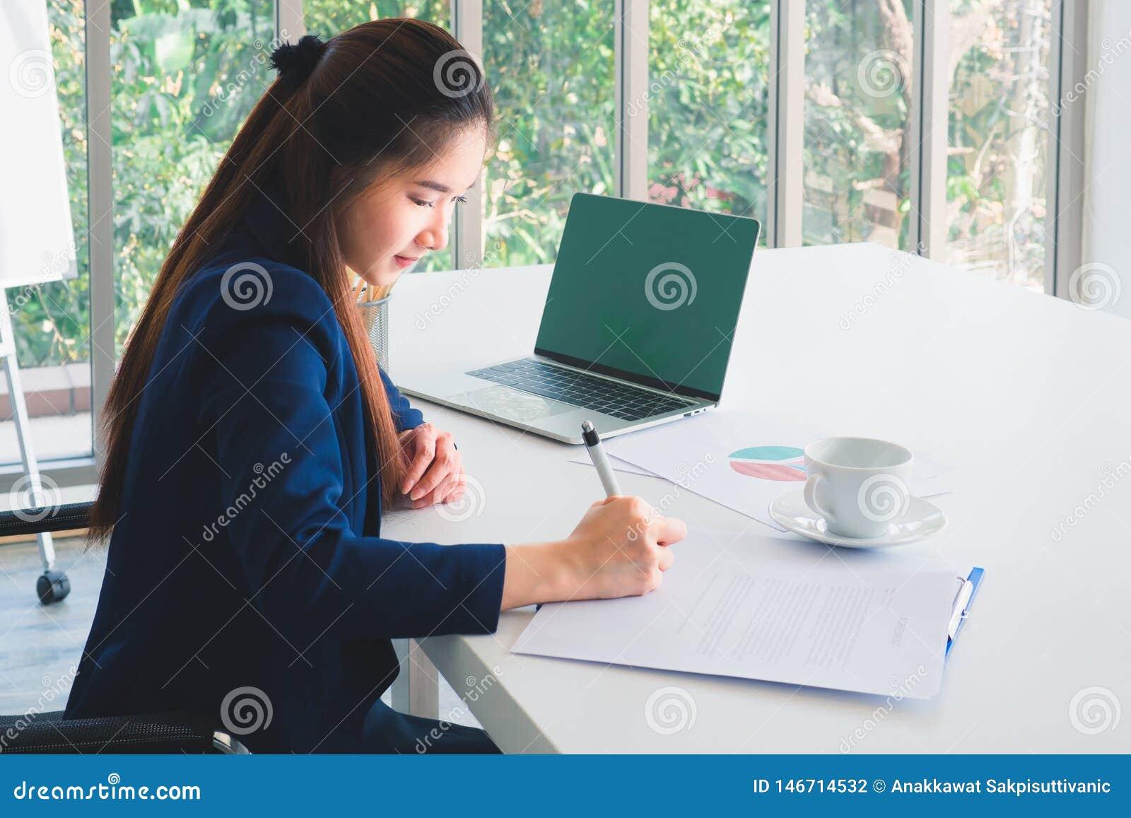 Ασιατική μακρυμάλλης όμορφη επιχειρησιακή γυναίκα στο μπλε ναυτικό κοστούμι που λειτουργεί, έγγραφο γραψίματος στον πίνακα στην α